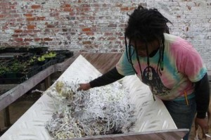 Ica tending to the compost bin inside the greenhouse at the St. Roch garden